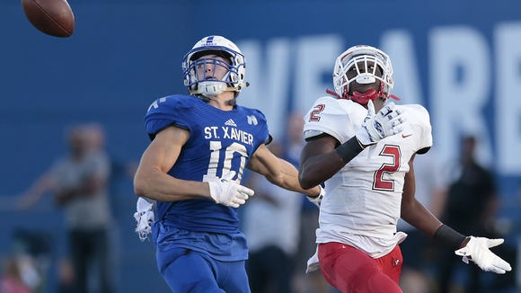 St. Xavier Bombers defensive back Colton Paul (10), left, and Colerain Cardinals wide receiver Amir Riep (2) eye a tipped ball in the first half during the high school football game between the Colerain Cardinals and St. Xavier Bombers, Friday, Sept. 2, 2016, at Ballaban Field in Cincinnati.
