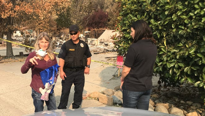 Kathy Case, left, who lost her home in the Carr Fire, talks to state officials who were in Redding on Wednesday to warn Carr Fire victims about potential scams.