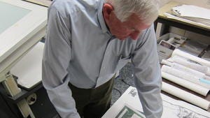 This photo taken May 3, 2013 shows John Sayles, 79, a planner at Stanley Consultants, reviewing a map from a New Orleans project he worked on, at the companyâ??s headquarters in Muscatine, Iowa. Sayles is among the employees at Stanley who have participated in â??phased retirement,â? in which a worker can cut back their hours in the months or years before their formal retirement, and continue to work part-time after.