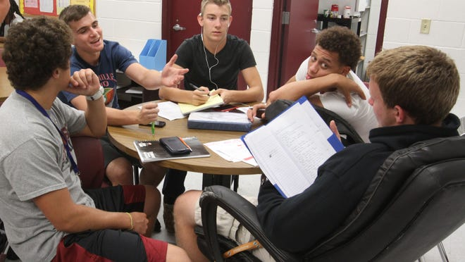 Football players at Riverdale High School work on helping each other with homework during a study hall .