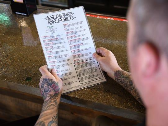 Nick Sinicropi of Art's Pub looks at the new menu Monday,