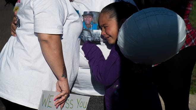 Jonathan Candelario's sister Jennifer Candelario, from left, mother Margaret Candelario and niece Jesyana Alicea, 7, mourn as a ceremony is held on the two year anniversary of his death Thursday, April 14 in Vineland.