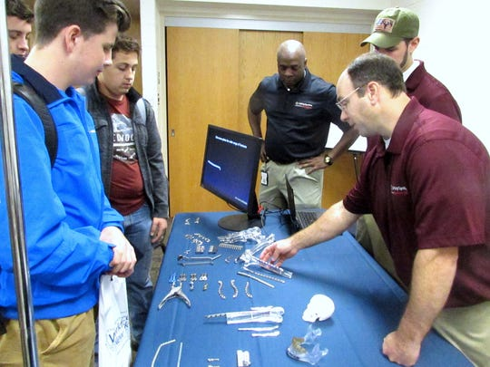 Dylan Jones, right, an engineering technician with Synthes, shows students some of the orthopedic products and tools the company makes at its Big Flats plant during a manufacturing expo Friday.
