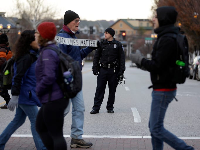 A police officer monitors protesters as they block