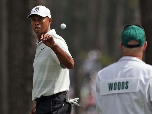 Tiger Woods, left, catches a ball tossed by his caddie Joe LaCava as he gets ready to putt on six during the second round of the Masters golf tournament at Augusta National Golf Club in Augusta, Ga., Friday, April 6, 2018. (Jason Getz/Atlanta Journal-Constitution via AP)
