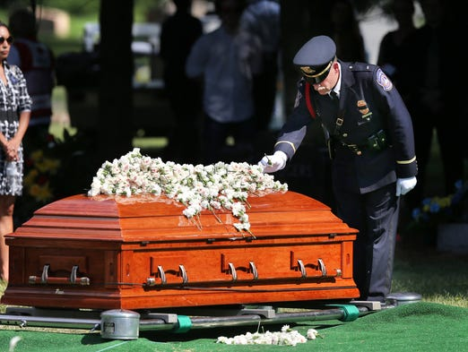Honor Guard Commander Don Weilhamer puts the final flower on the casket of fallen IMPD Police Officer Perry Renn at the end of the ceremony held at Crown Hill Cemetery in Indianapolis on Friday, July 11, 2014.