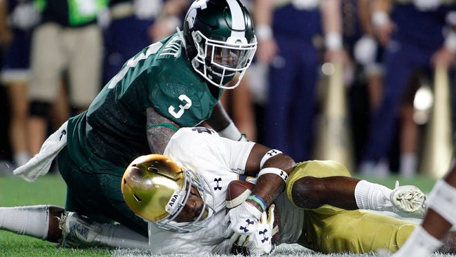 Notre Dame's Shaun Crawford recovers a fumble in the end zone for a touchback after stripping the ball from Michigan State's LJ Scott (3) in the second quarter Sept. 23, 2017 in East Lansing.
