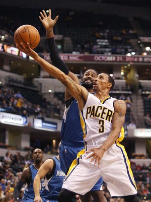 Indiana Pacer George Hill drives to the basket past Minnesota Timberwolves' Ronny Turiaf in the first half half of their first preseason game at Bankers Life Fieldhouse in Indianapolis on Tuesday, October 7, 2014. The Pacers led 46-42 at the half.