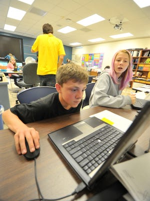 Middle school students Mitchell Tesch, left, and Destinie Juers, both of Wausau, work on school work on computers at the Enrich, Excel, Achieve Learning Academy in 2014.