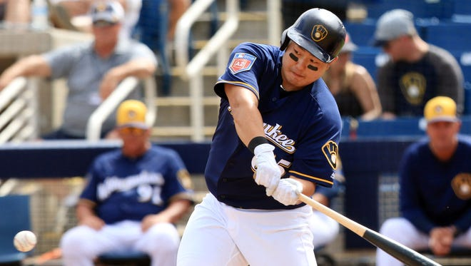 Ji-Man Choi of the Brewers keeps his eyes to the ball before connecting for a single against the Diamondbacks on Thursday.