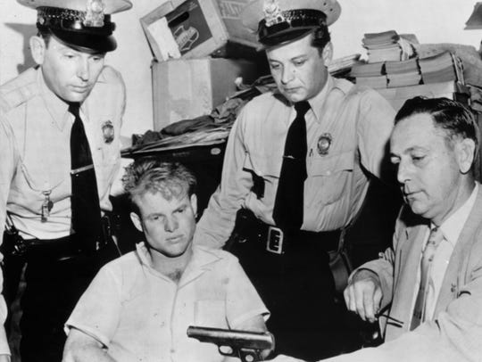Victor H. Lively, a suspect in an Indianapolis slaying, disconsolately eyed the .32-caliber automatic pistol he was carrying when picked up on July 23, 1954, by police near Clayton, Mo.