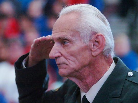 Army veteran Jim Laboda salutes during the ceremony. His grandson, Aiden Laboda, attends OLS.