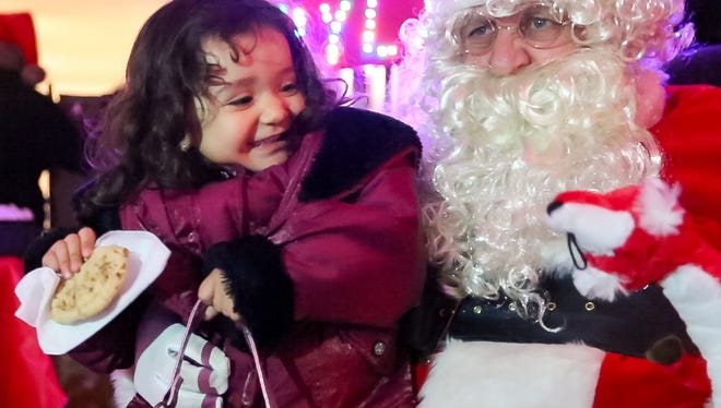 Juliette Oliver, 2, of Las Cruces, visits with Santa on Friday, Dec. 22, 2017, during a holiday party at the home of Jessie Giron. The event was open to the public, where over 60 blow up Christmas displays and a large amount of lights were on display.