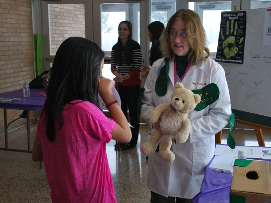 Dryden Middle School nurse Cindy Price teaches sixth-grader Jenny Ngyuyen about germs and how easily they are spread.
