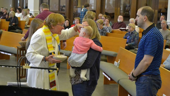 The Rev. Lori Swenson, left, applies the sign of the cross on the forehead of Allison, 1-year-old daughter of parishioners Aaron, right, and Andrea Moede, during communion at a service at Ascension Lutheran Church in Allouez on Sunday, May 1, 2016. Andrea is holding Allison. Swenson and her husband, Luther, have been the pastors at Ascension Lutheran since 1995.