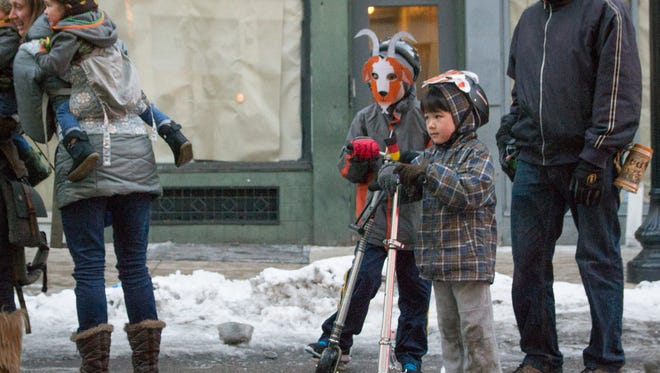 Ren, right, and Rui Prows wear homemade goat masks as they watch the 2015 Bockfest Parade pass them on Main Street Friday evening.