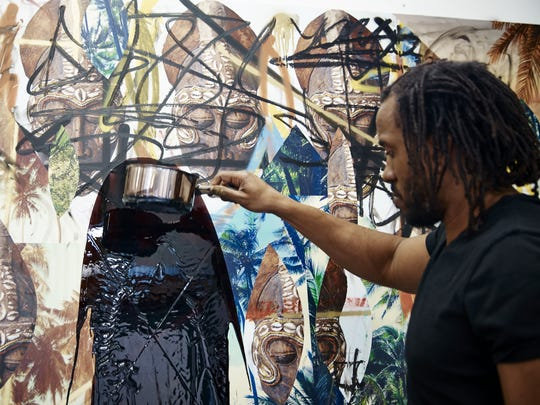 Artist Rashid Johnson works on one of his Escape Collages. Johnson's work is on display at the Milwaukee Art Museum.
