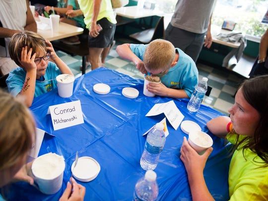Conrad Milchanoski, 9, holds his head while taking a break from his ice cream as Kenny Knowles, 9, continues to eat during the Brain Freeze Ice Cream Eating Contest on Sunday, July 16, 2017, at Royal Scoop in Bonita Springs. Knowles won the 10 and under division, eating a pint of ice cream in 6 minutes and 21 seconds.