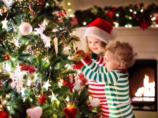 kids decorating christmas tree in beautiful living room - What To Do Christmas Day
