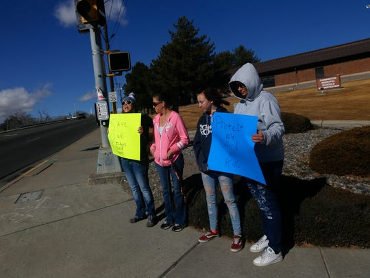 From left, Holly Gregory, Karlene Heath Briann Heath and Rose Hensley hold signs that support allowing teachers to have concealed firearms in school. The protest they attended was on Monday in Farmington.