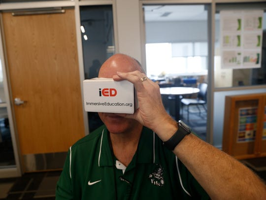 Farmington High School Assistant Principal Rocky Moore looks through virtual reality viewer to view a photo of a classroom Friday during a seminar on programing and coding through gaming at Farmington High School.