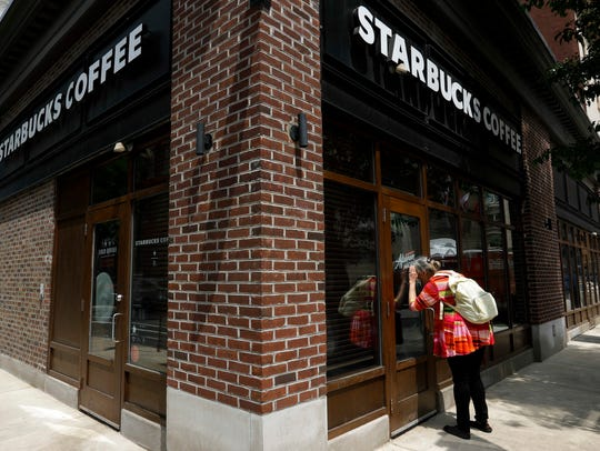 A woman peers into a closed Starbucks Coffee shop,