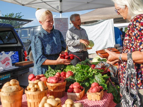 Victoria Kaufman helps customers select produce Saturday at the Kaufman Family Farm booth during the Farmington Growers Market outside the Farmington Museum at Gateway Park.