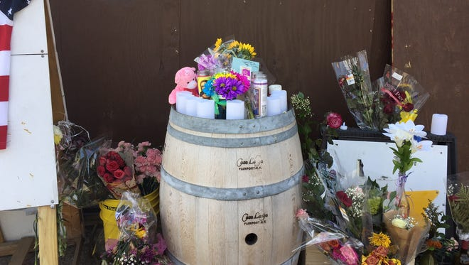 Bouquets of flowers adorn the outside Char's South Ave. Wine and Liquor where owner Charlotte Lahr was killed Thursday afternoon.