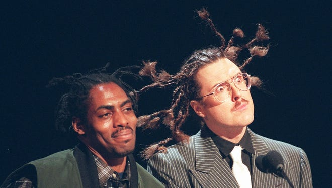 """Rap artist Coolio and pop music satirist """"Weird Al"""" Yankovic, with a Coolio hairdo, appear at the podium presenting the favorite alternative artist award to the group Pearl Jam, at the 23rd annual American Music Awards on Jan. 29, 1996, in Los Angeles. Coolio also won an award for favorite Rap-Hip Hop artist."""