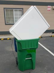 A Waste Management trash collector found this washing machine sticking out of a recycle bin and took the picture to show to Waste Management's customer ombudsman.