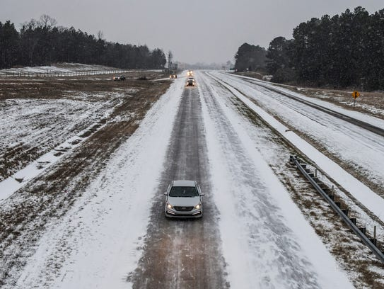 Traffic makes its way north on Highway 7 as snow falls