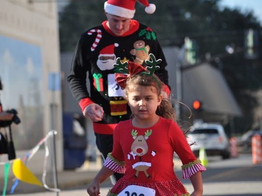 Sophia Davis, 5, crosses the finish line with dad Trey after completing the Alex Winter Fete Ugly Sweater 5K.