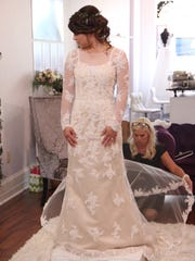 "Renee Miller, right, helps Tori Bates try on a wedding dress during an episode of ""Bringing Up Bates."""