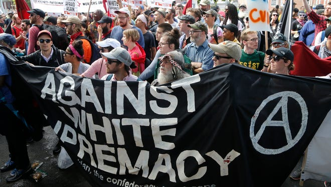 Demonstrators hold a banner decrying white supremacist's at the entrance to Emancipation Park in Charlottesville, Va., on Aug. 12, 2017.