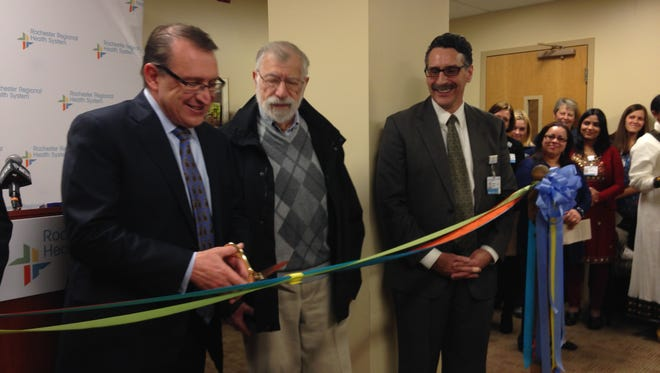 Eric Bieber, left, president and CEO of the Rochester Regional Health System, cuts the ribbon for the launch of the new Center of Refugee Health.
