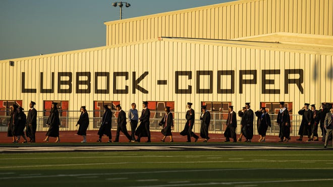 Lubbock-Cooper graduates walk out for the processional at the Lubbock-Cooper High School 2020 graduation on Friday, June 5, 2020, at Pirate Stadium in Woodrow, Texas.