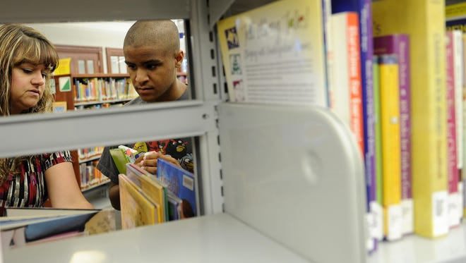 Loretta Naylor and Mac Croom look through shelves in the Licking County Library for books to read over the summer before school starts.