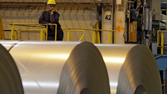 An employee looks on from behind coils of steel at ArcelorMittal Steel's hot dip galvanizing line in Cuyahoga Heights, Ohio. President Donald Trump's tariffs are expected to raise prices for steel and aluminum in this country.