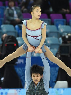 Narumi Takahashi and Ryuichi Kihara of Japan skate past a whole lot of empty seats at the Iceburg on the first full day of the Sochi Winter Games.