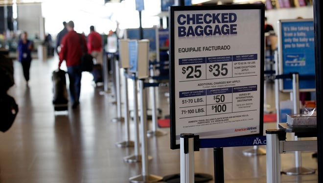 This file photograph from June 7, 2010, shows an American Airlines sign listing the fees for checked baggage at Seattle-Tacoma International Airport.