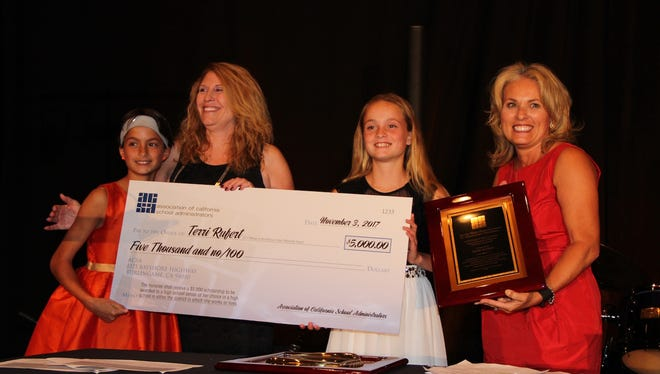 Association of California School Administrators President Lisa Gonzales, right, had her daughters Kennedy, left, and Landry, make the award presentation to Terri Rufert.