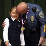 Reese Scott lgets a kiss from her hero, her uncle Shawn Waldron as Our Lady of Mercy celebrates their first annual Heroes award recognizing outstanding adults in their student's lives who epitomize good role models. February 11, 2016, Whippany, NJ.