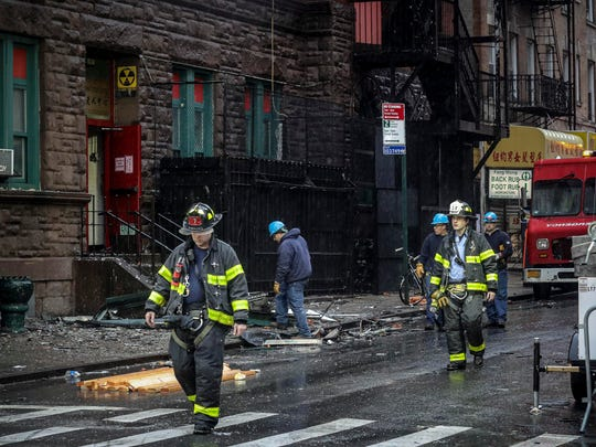 Firefighters leave a building Saturday that houses several nonprofits and a senior center but was destroyed by fire overnight in New York's Chinatown neighborhood.