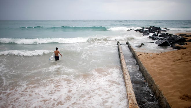 A surfer enters the water to take advantage of the high waves in San Juan, Puerto Rico on Saturday. Bertha pushed just south of Puerto Rico on Saturday as it unleashed heavy rains and strong winds across the region.