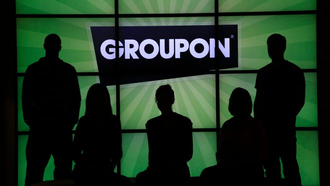 In this Sept. 22, 2011, photo, employees at Groupon pose in silhouette by the company logo in the lobby of the online coupon company's Chicago offices.