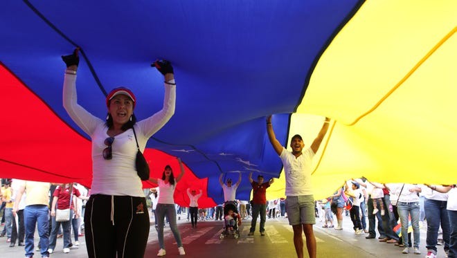 Venezuelans stand under their nation's flag as they protest against the government of President Nicolas Maduro at the Angel of Independence Monument in Mexico City, Sunday. Venezuela's opposition has been protesting crime and inflation, and Maduro has called for peace talks to end rioting.