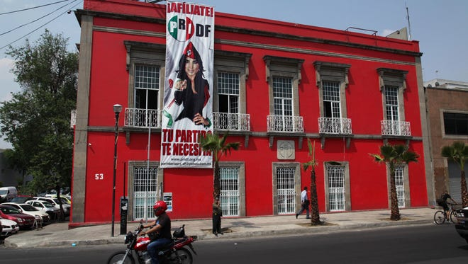 A sign promoting the Institutional Revolutionary Party (PRI) hangs on the PRI headquarters for Mexico City, Wednesday, April 2, 2014.