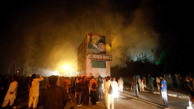 Pakistani protesters gather around a container with portrait of Pakistan's anti-government cleric Tahir-ul-Qadri as police fire tear gas shell to disperse them during clashes in Islamabad, Pakistan,on Aug. 31, 2014.