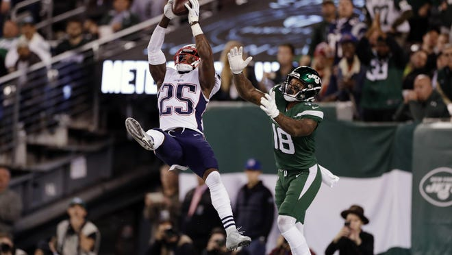 New England Patriots' Terrence Brooks (25) intercepts a pass to New York Jets' Demaryius Thomas (18) during the second half.