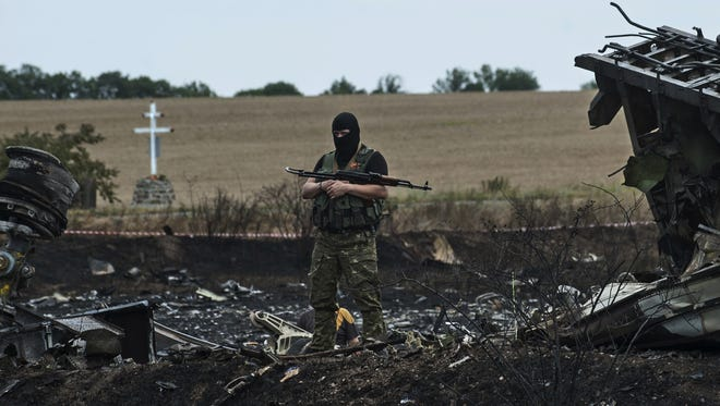 A pro-Russian fighter guards the crash site of Malaysia Airlines Flight 17 near the village of Hrabove, eastern Ukraine, Sunday, July 20, 2014. Rebels in eastern Ukraine took control Sunday of the bodies recovered from downed Malaysia Airlines Flight 17, and the U.S. and European leaders demanded that Russian President Vladimir Putin make sure rebels give international investigators full access to the crash site.